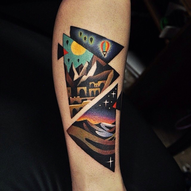 Old school big triangle shaped arm tattoo stylized with various night countrysides