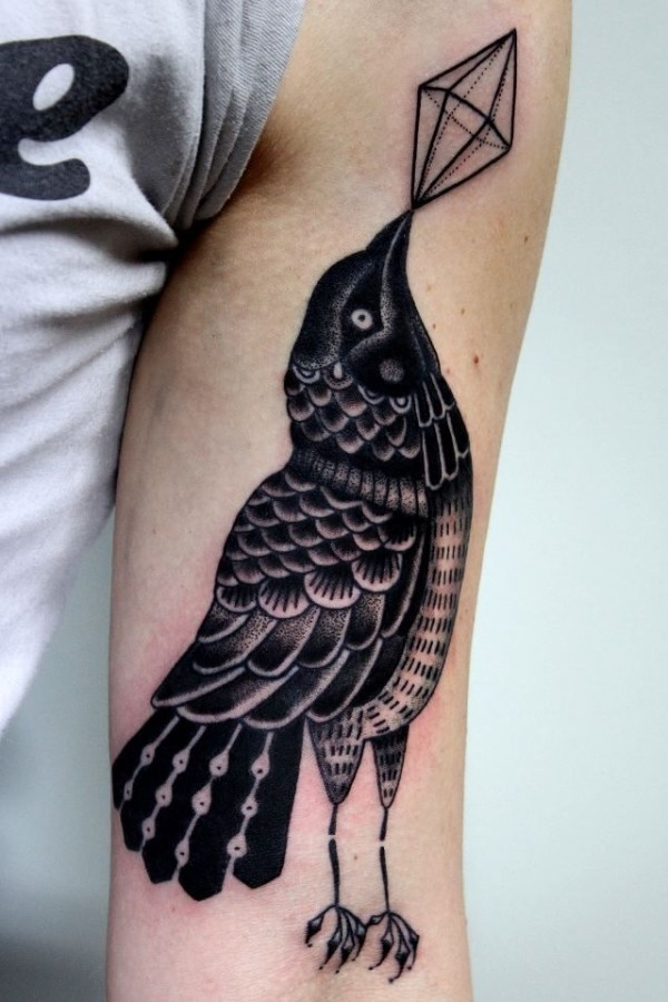 Old school black and white crow tattoo on arm with geometrical figure