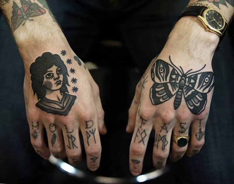 Old school black and white man portrait with butterfly tattoo on hands with lettering