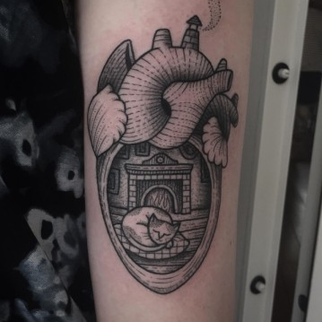 Old school black ink heart shaped tattoo on arm stylized with sleeping cat