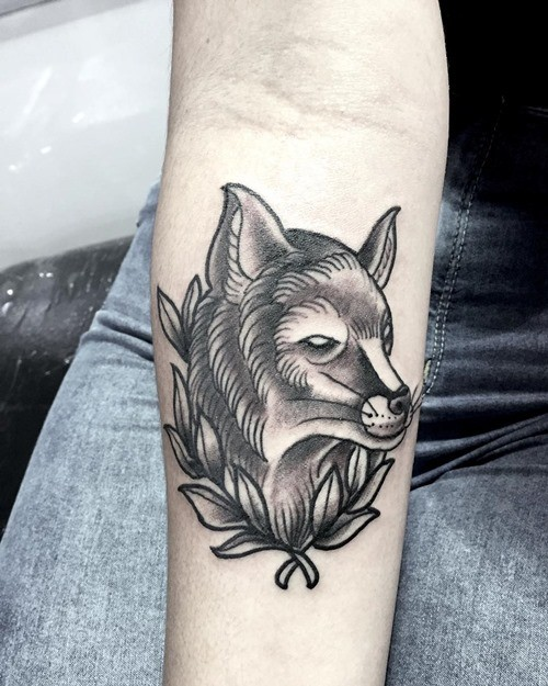 Old school black ink mystical fox tattoo on forearm with leaves