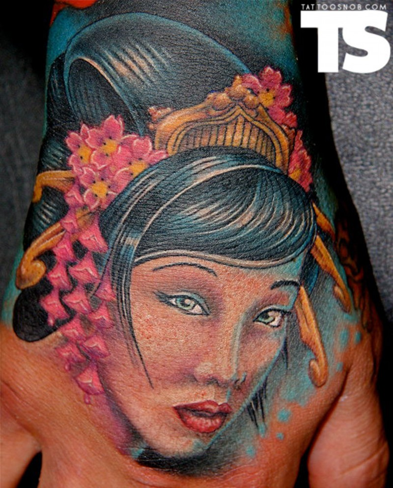 Old school cartoon like colored hand tattoo of beautiful Asian woman with flowers in hair