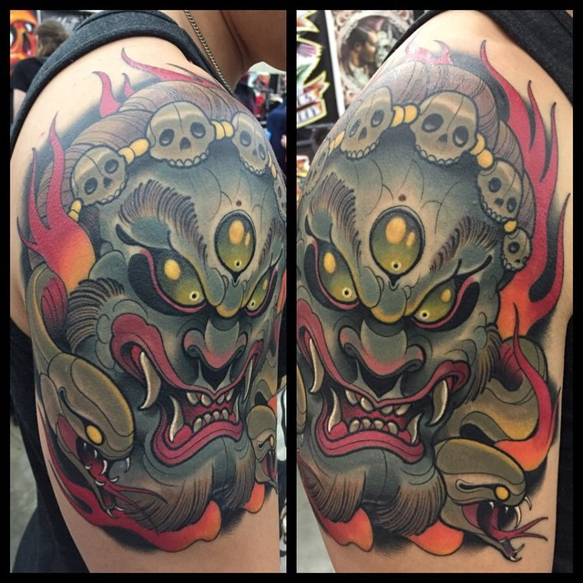 Old school cartoon style colored evil monster on shoulder tattoo with snakes