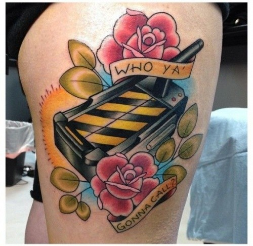 Old school coll painted and designed colored Ghostbusters themed tattoo on thigh with flowers and lettering