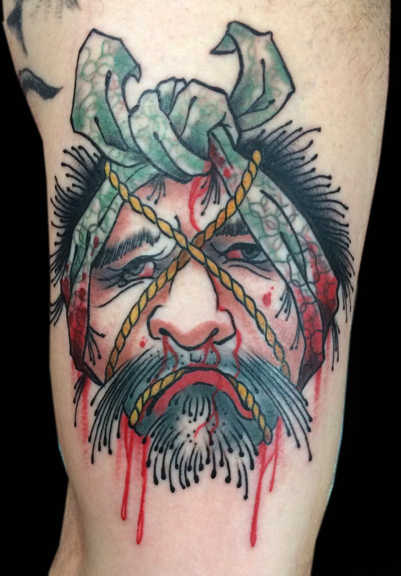 Old school colored arm tattoo of bloody Asian man severed head
