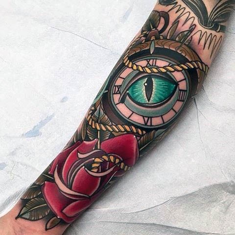 Old school colored mystical compass with eye tattoo on forearm with red rose