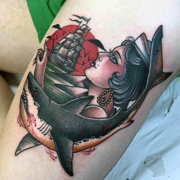 Old school colored sailor woman tattoo on thigh combined with bloody shark and sailing ship