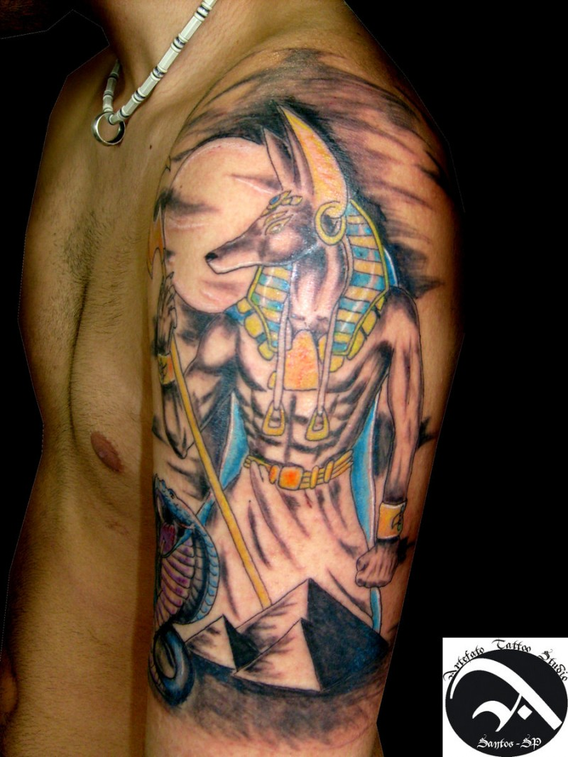 Old school colored Seth God tattoo on shoulder combined with snake and pyramids