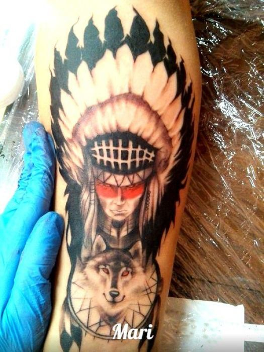 Old school colorful demonic Indian tattoo on forearm stylized with wolf and dream catcher