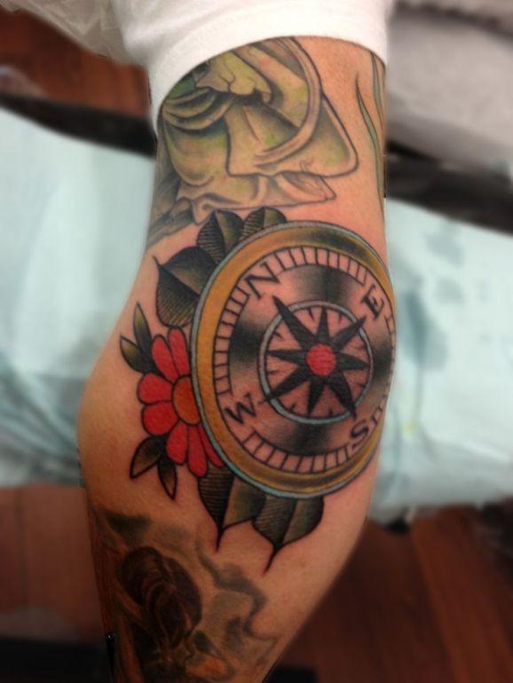 Tatuaggio colorato di vecchia scuola sul braccio la bussola & i fiori