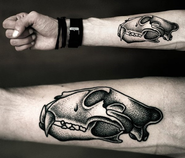 Old school dot style forearm tattoo of ancient animal skull