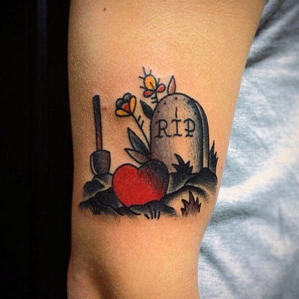 Old school gravestone colored tattoo with heart and spade on arm