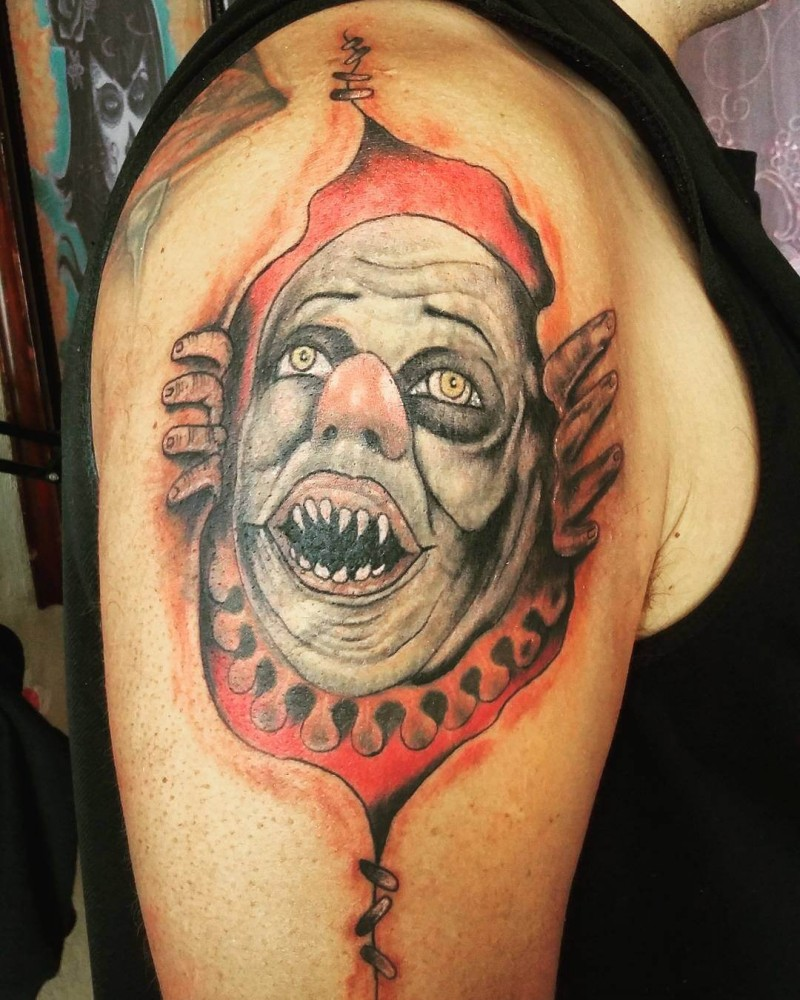 Old school illustrative style colored ripped skin tattoo on shoulder with demonic clown face