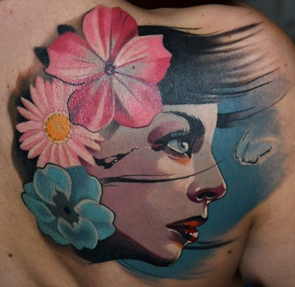 Old school multicolored woman face tattoo on upper back with flowers and butterfly