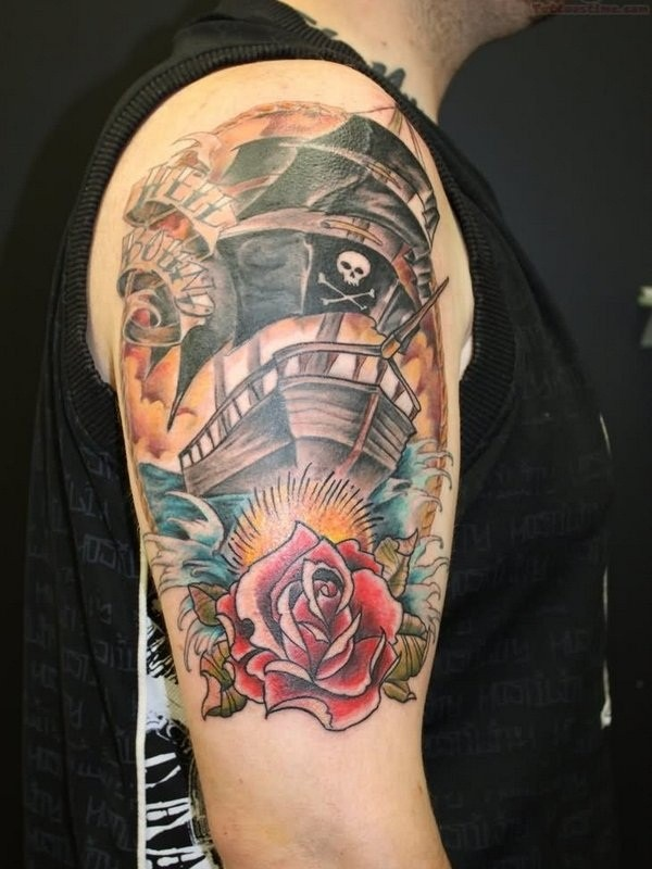 Old school nautical themed on shoulder tattoo of pirate ship with rose and lettering