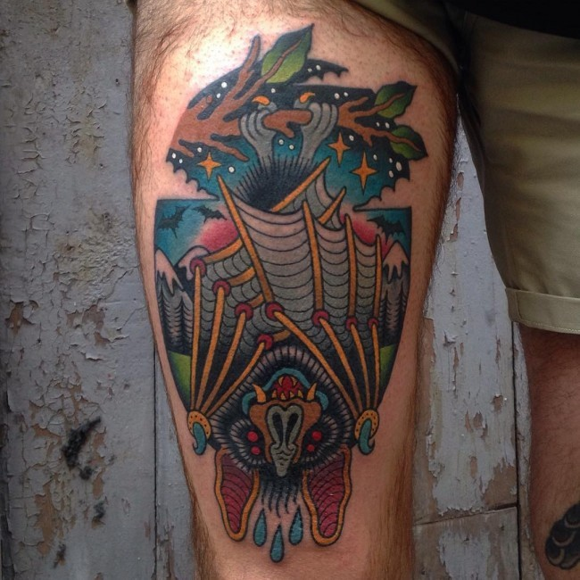 Old school painted and colored bat tattoo on thigh stylized with night sky