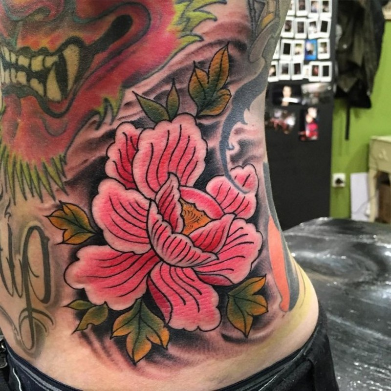 Old school pink colored flower tattoo on side