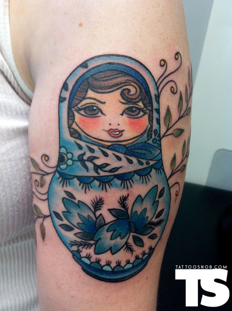Old school simple designed and colored matryoshka tattoo on shoulder stylized with leaves