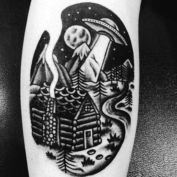 Old school style black and white alien ship in night sky above the house tattoo on leg