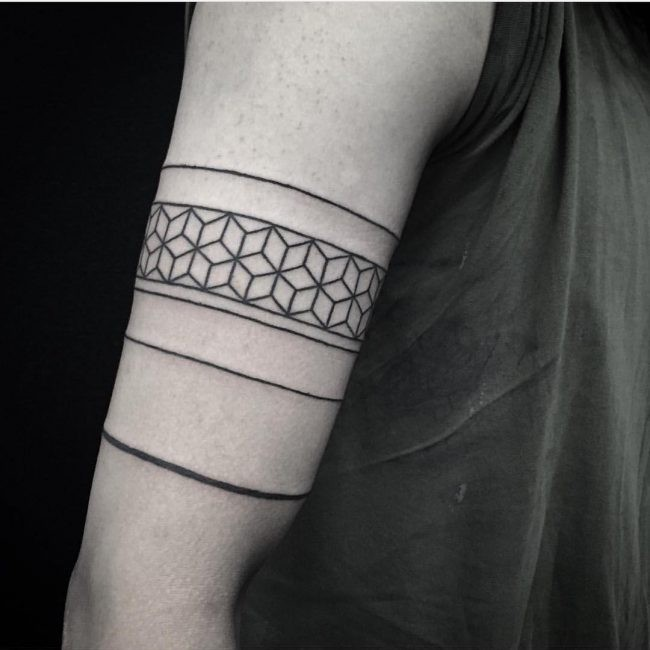 Old school style black ink biceps tattoo of geometrical ornaments