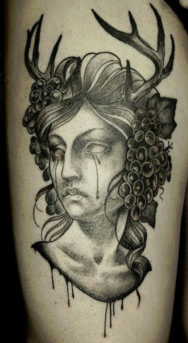 Old school style black ink crying woman portrait tattoo on thigh combined with horns and grape