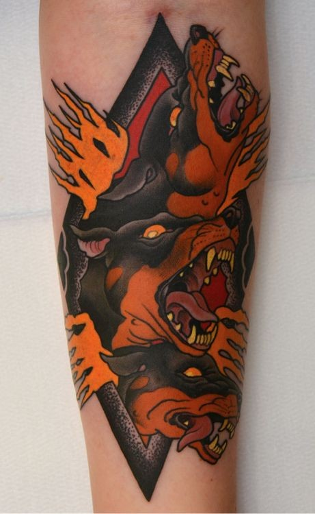 Old school style black ink hell dogs tattoo on forearm with flames