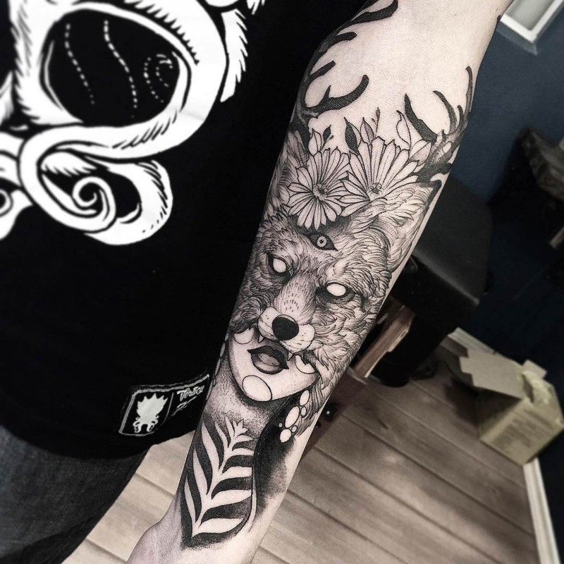 Old school style black ink unusual woman in fox mask with horns tattoo on forearm stylized with flowers