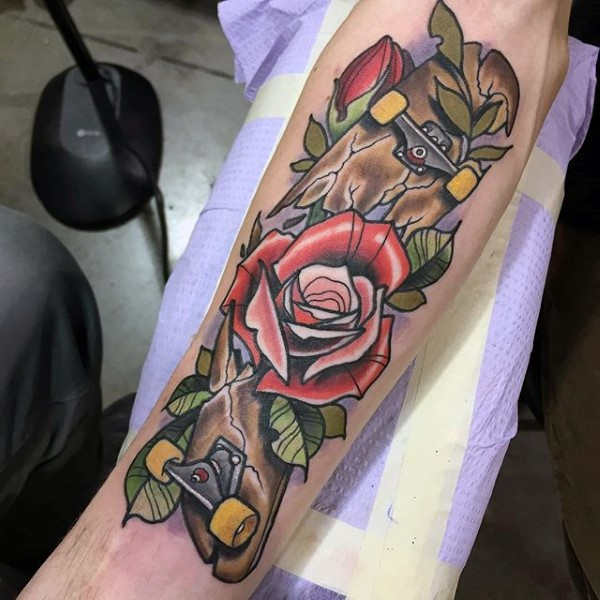 Old school style broken skateboard and red roses forearm tattoo with pale violet haze