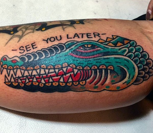 Old school style colored alligator head with lettering tattoo on arm