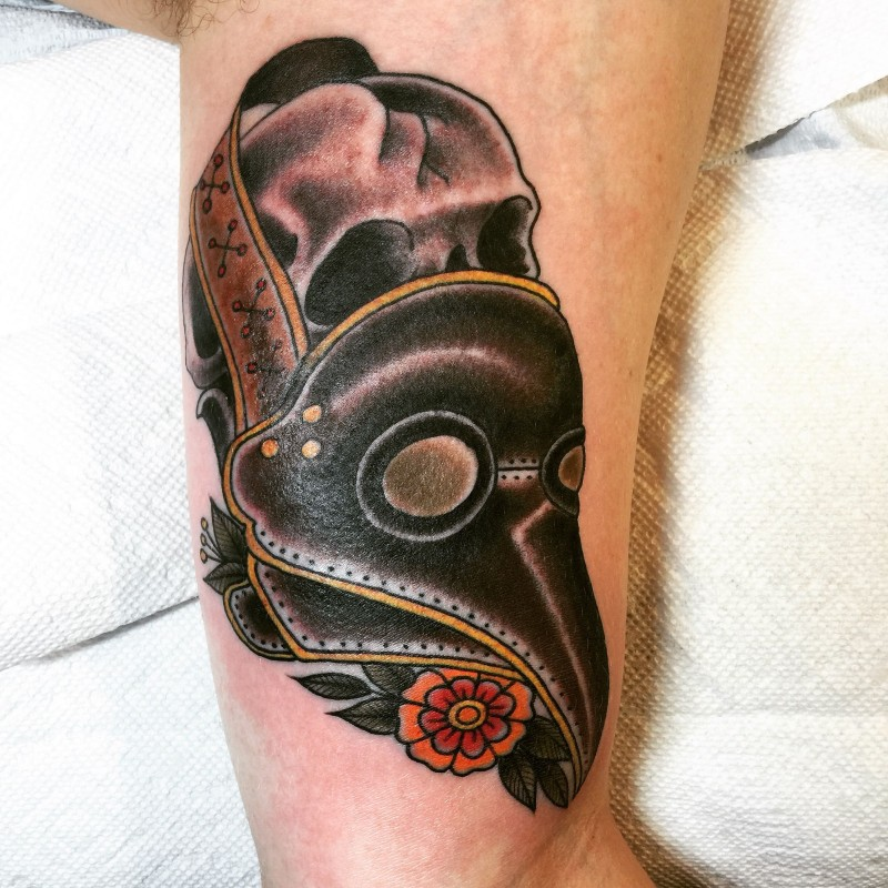 Old school style colored arm tattoo of human skull with plague doctors mask and flowers