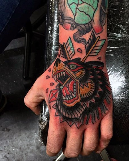 Old school style colored bear head with arrows tattoo on hand