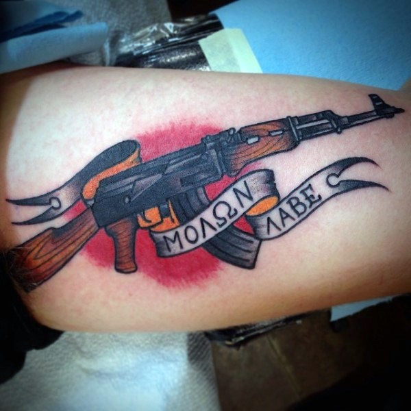 Old school style colored biceps tattoo of AK rifle with lettering