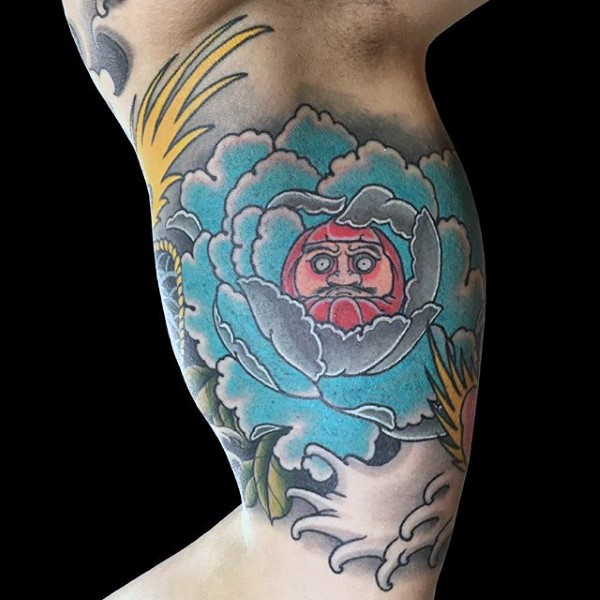 Old school style colored biceps tattoo of big flower stylized with daruma doll