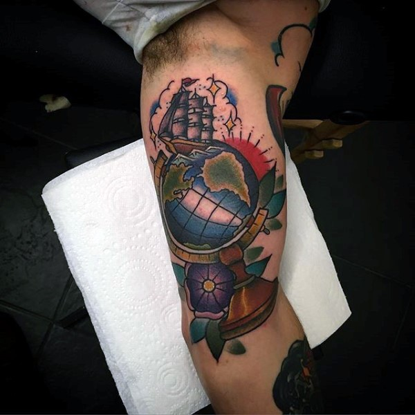 Old school style colored biceps tattoo of little ship with globe and flowers