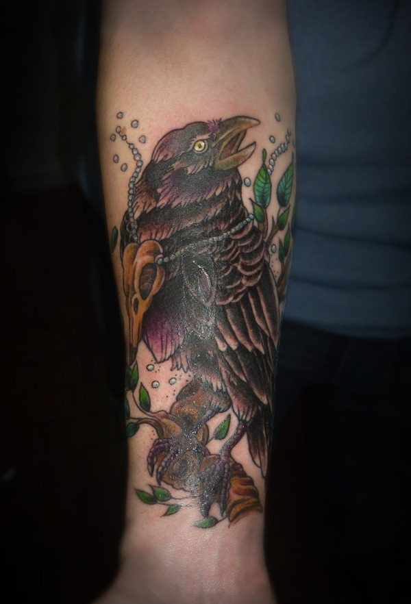 Old school style colored big crow tattoo on forearm stylized with leaves and animal skull