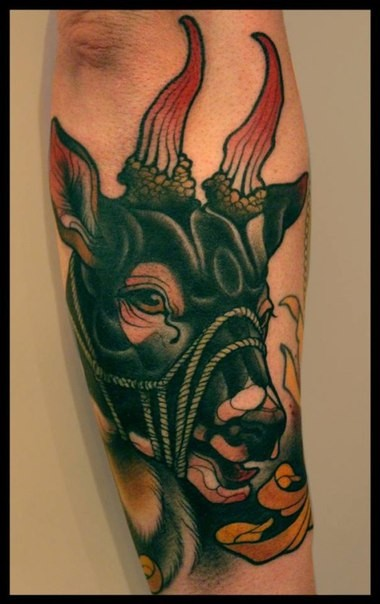 Old school style colored forearm tattoo of demonic goat