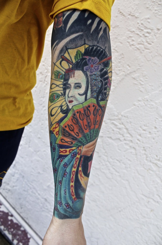 Old school style colored forearm tattoo of geisha woman with fan