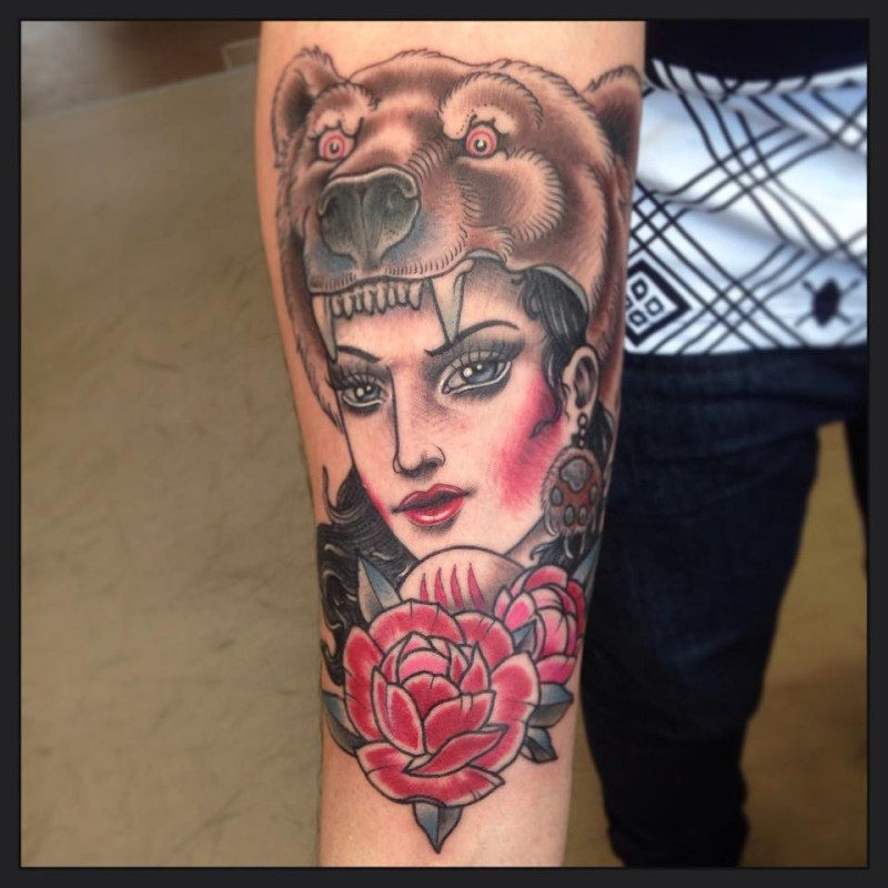 Old school style colored forearm tattoo of beautiful woman with rose and bear helmet