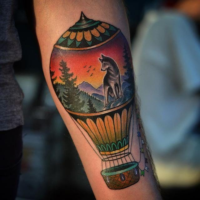 Old school style colored forearm tattoo of balloon stylized with wolf in mountain forest