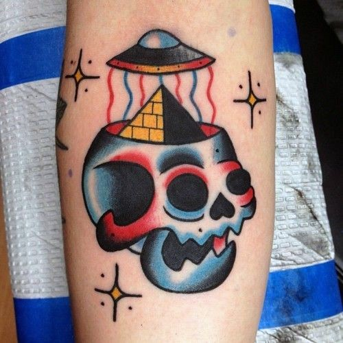 Old school style colored funny skull with alien ship and pyramid tattoo on arm