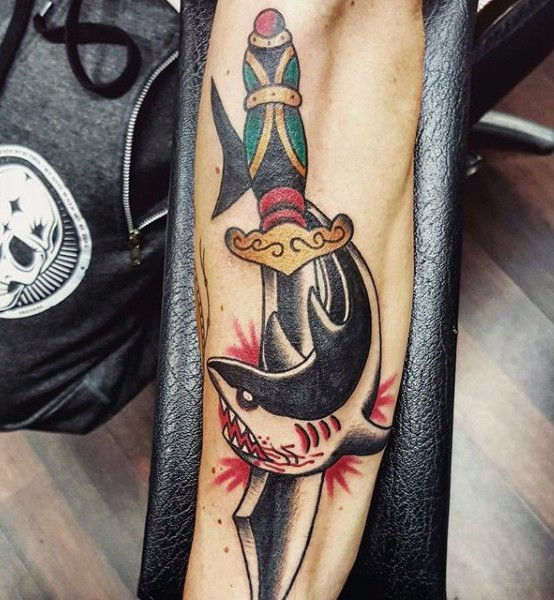 Old school style colored knife with shark tattoo on arm
