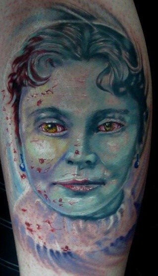 Old school style colored leg tattoo of vampire woman face