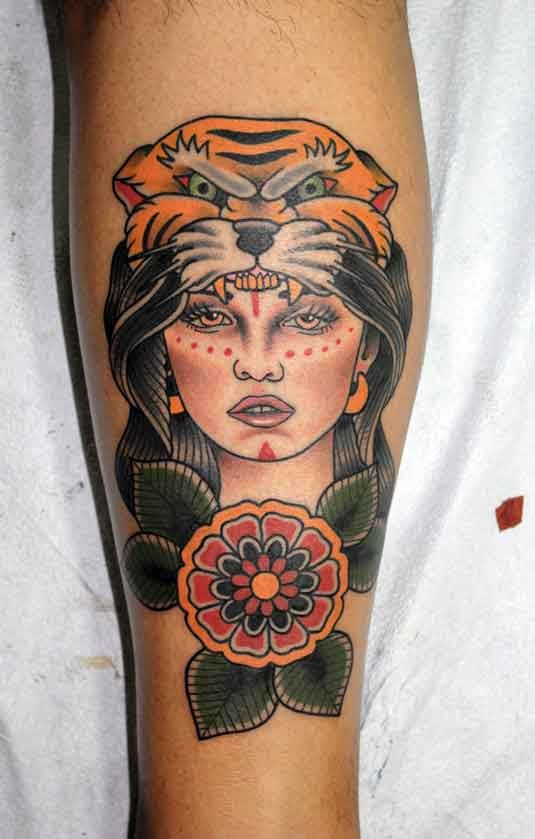 Old school style colored leg tattoo of woman with tiger helmet and flowers