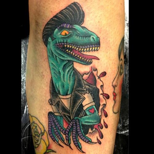 Old school style colored leg tattoo of Elvis like dinosaur