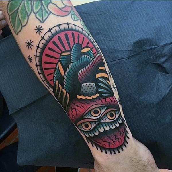 Old school style colored mystical human heart tattoo on forearm