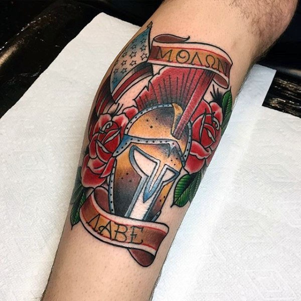 Old school style colored Roman warrior helmet with flowers and lettering tattoo on arm