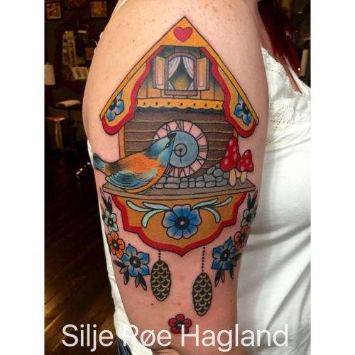 Old school style colored shoulder tattoo of wooden clock with bird and flowers