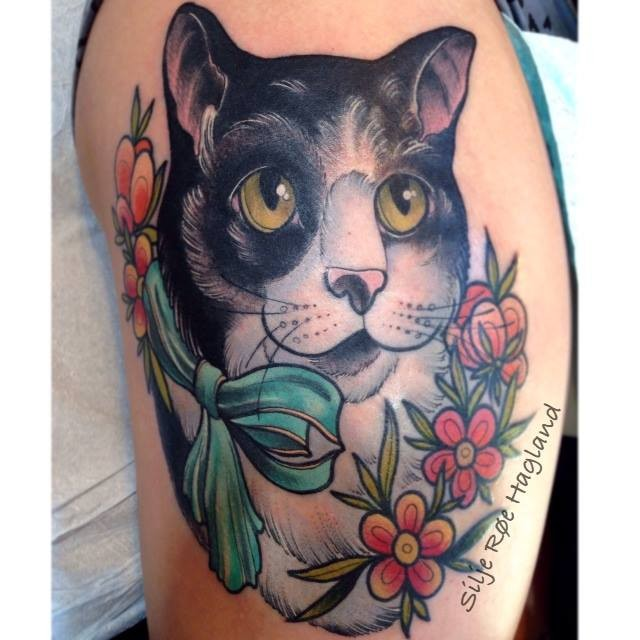 Old school style colored shoulder tattoo of cat face with bow and flowers