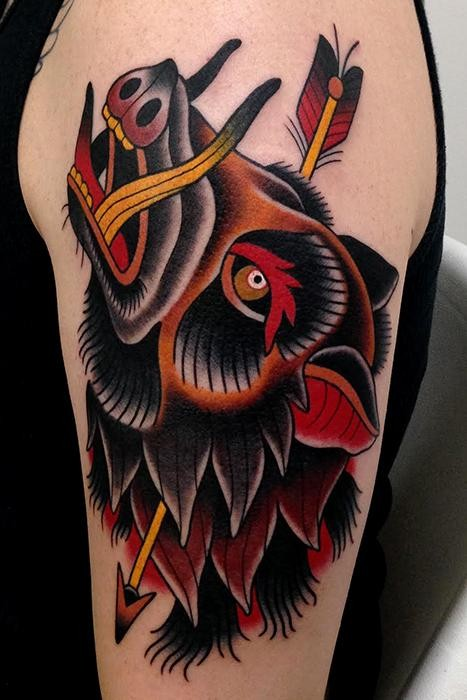 Old school style colored shoulder tattoo of boar with arrow