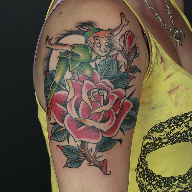 Old school style colored shoulder tattoo of Peter Pan and rose flower